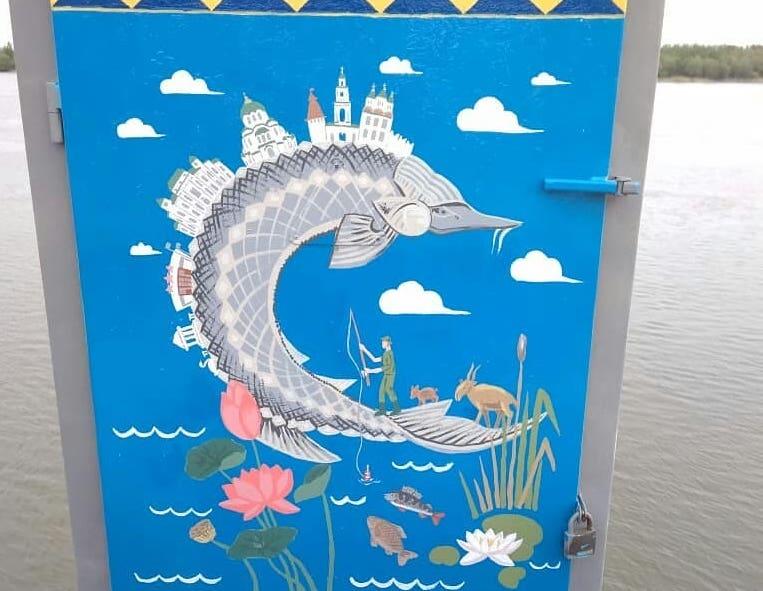 Астраханки нарисовали осетра за перилами набережной