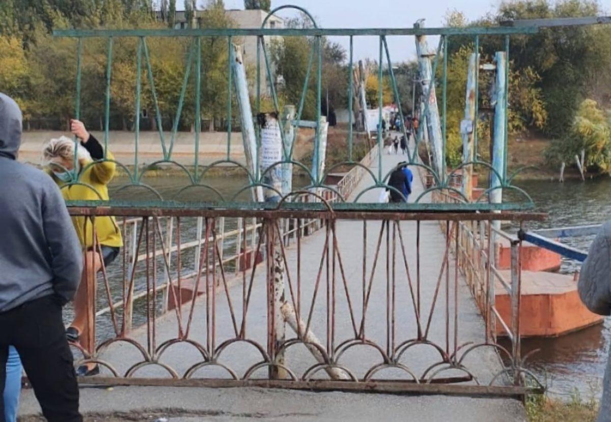 Жители Десятки пытаются перелезть на закрытый мост через ограждения
